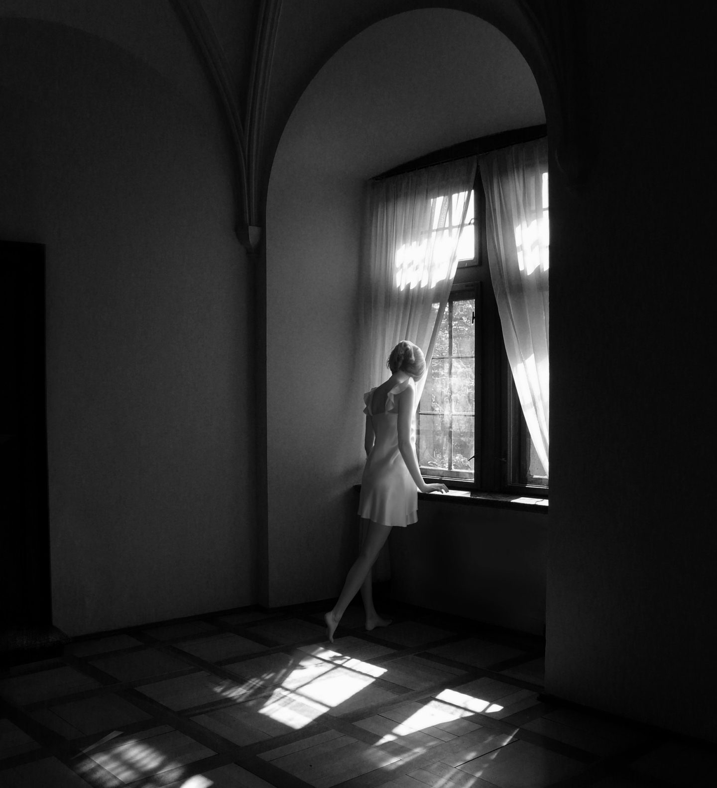 black and white photo of woman staring out of a window