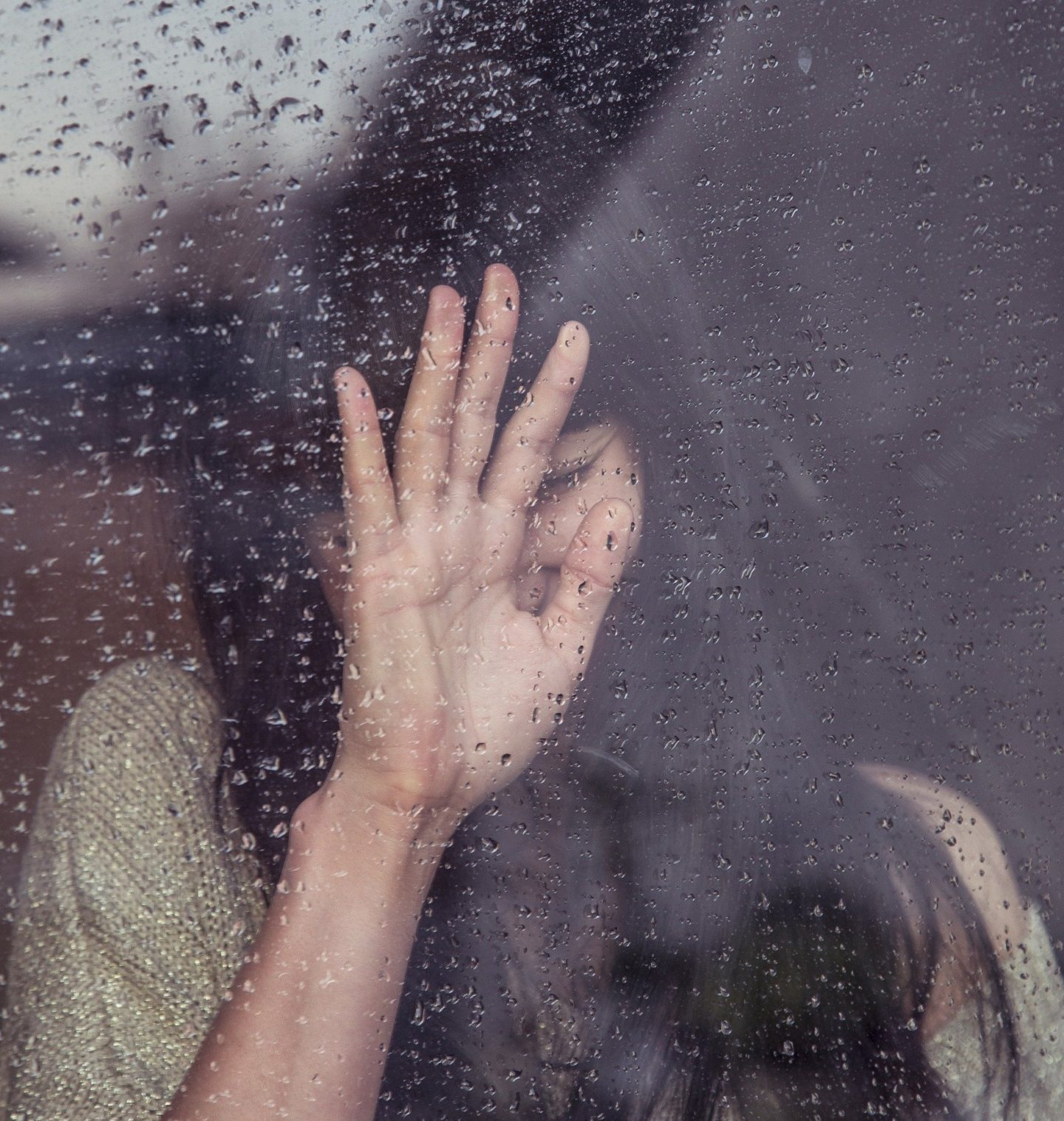 girl crying while touching glass window