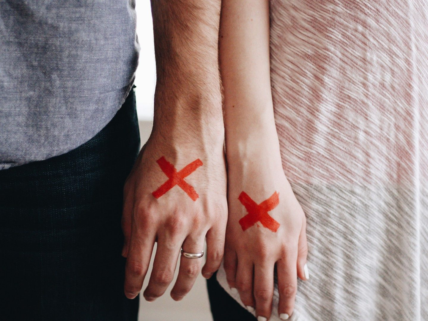 a man and woman hands almost touching both with a red cross on the back of them